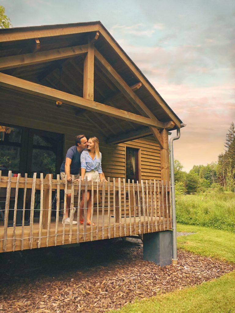 Koppel op de porch van hun cabin in La Truite d'Argent in Houffalize